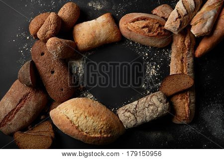 Top view of blank copy space represented among different kinds of breads. Different bread sorts for your taste. Variety of different kind of breads, food industry.