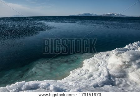 Ice coast and blue water of the Okhotsk Sea in winter Magadan region