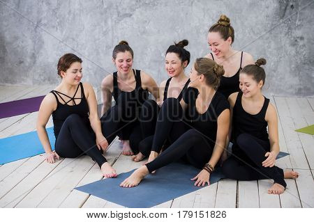 Smiling yogi girl exercising, having a break at class, group of friends watching on the phone.