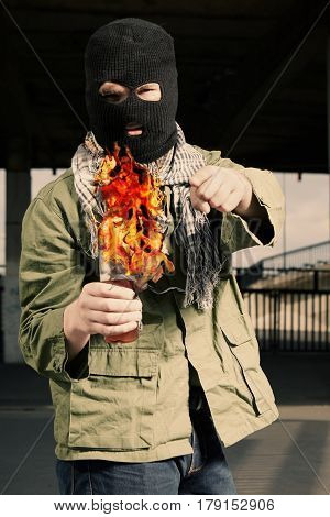Man in balaclava lighting a flammable bottle before throwing