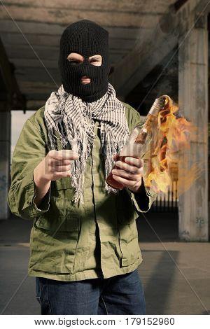 Man in balaclava lighting flammable bottle in hand