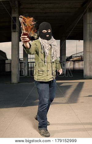 Man in balaclava throwing a flammable bottle