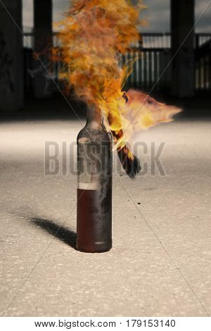 Burning flammable bottle with rags on ground
