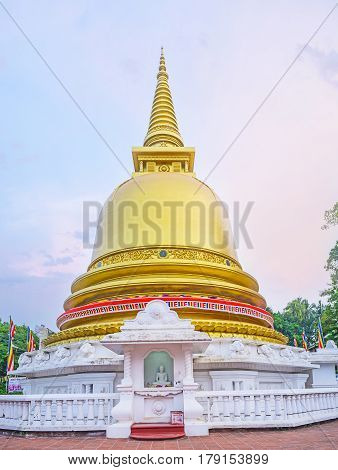 The gilt Pagoda of Dambulla Golden Temple with the statue of Meditating Lord Buddha at the altar Sri Lanka.