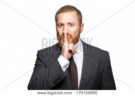 Serious businessman with finger on lips making silence gesture. Shh!!! isolated on white background looking at camera.