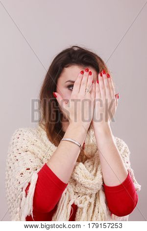 Elegant woman covering her face with hands showing red varnish nails