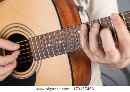 A picture of an acoustic guitar classical color in the hands of a guitarist with a clamped chord. Both hands in the frame