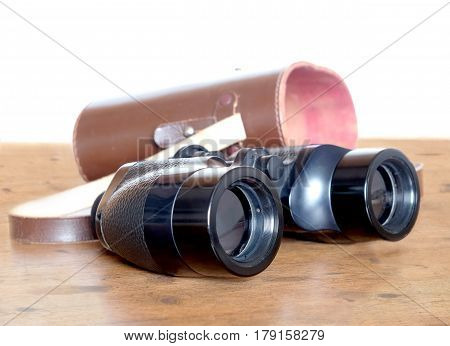 Vintage english military Porro prism black color binoculars and opened brown hard leather carry case on wooden background over white side view indoor closeup