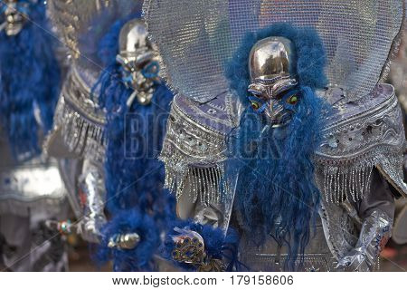 ORURO, BOLIVIA - FEBRUARY 25, 2017: Masked Morenada dancers in ornate costumes parading through the mining city of Oruro on the Altiplano of Bolivia during the annual carnival.