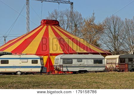Bright colored tent circus and white trailers
