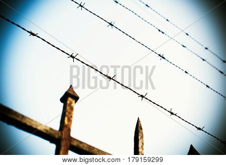 Prison fence in barbed wire fence closeup - security escape concept