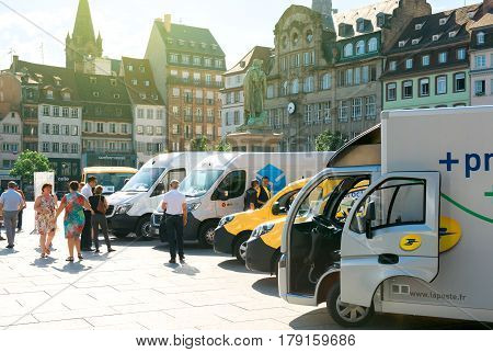 STRASBOURG FRANCE - JUN 24 2016: Fleet of Postal delivery electric cars and vans in a row in central Square Place Kleber early in the morning. La Poste is France's leading employer with a total workforce of 300000 working in postal shipping and banking br