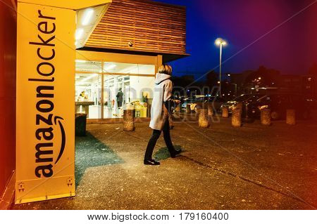 PARIS FRANCE - FEB 15 2017: Customer leaving Amazon locker orange delivery package locker at dusk - Amazon Locker is a self-service parcel delivery service offered by online retailer Amazon.com.