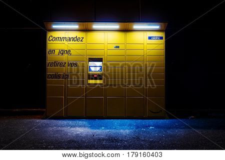 PARIS FRANCE - FEB 15 2017: night view over an Amazon locker orange delivery package locker at dusk - Amazon Locker is a self-service parcel delivery service offered by online retailer Amazon.com