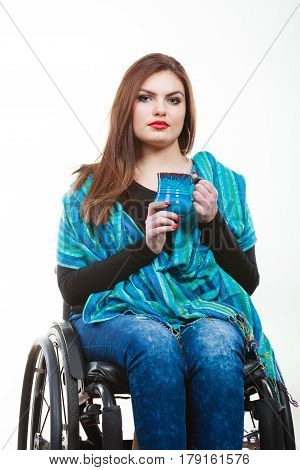 Dronk beverage disability happiness joy concept. Smiling disabled lady. Young crippled girl sitting on wheelchair holding blue cup.