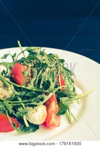 Fresh summer salad with tomatoes fresh arugula leaves and mini mozzarella cheese on white plate over dark wooden baclground with place for text. Healthy diet food concept. Copy space.