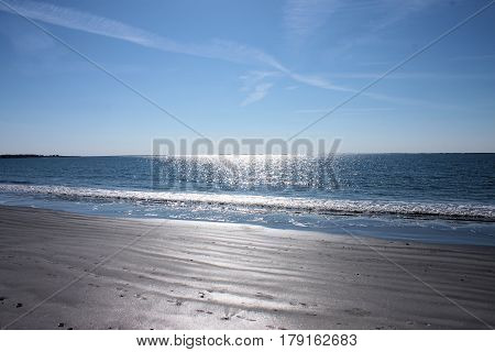 Low tide and calm waters of a beach on a cold sunny winter day.