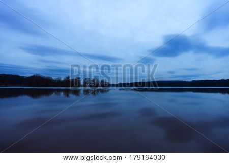 Late evening blue land and sky reflected like a mirror in calm lake tranquil scene
