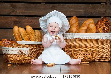 Child cooks eating a bagel on the background of baskets with rolls and bread