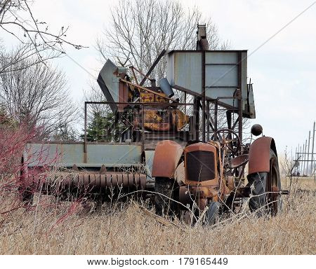An old abandoned combine and tractor in grove of trees.