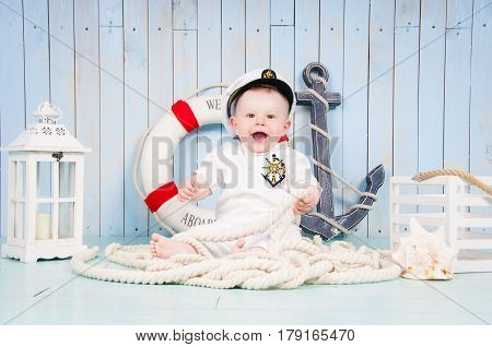 A little cheerful boy captain in the maritime interior.