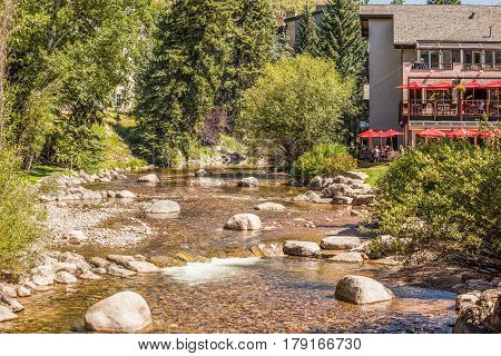 Vail, USA - September 10, 2015: Gore creek in Colorado with boulders and cafe