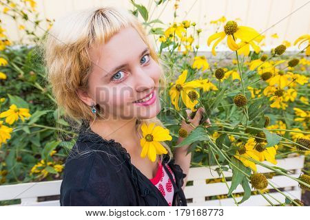 Closeup of young woman smiling by tall sunflower yellow daisy flowers on bench