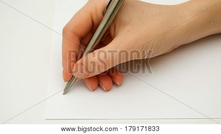 Female hand writes on the blank sheet of white paper