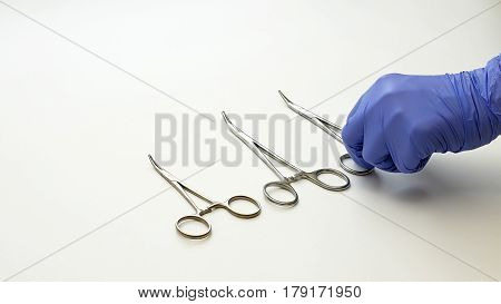 Surgical nurse in protective gloves prepares and puts medical surgery tools on table