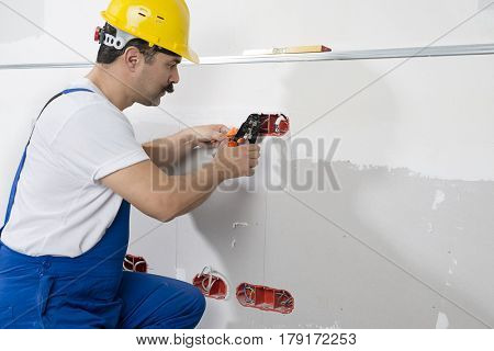 Electrician wearing overalls installing electricity outlet.