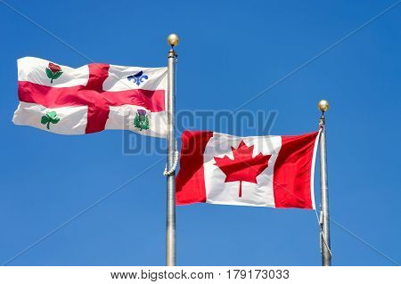 Canadian flag and Montreal city flag waving over blue sky