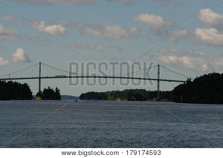bridge island water sky  clouds  trees  blue