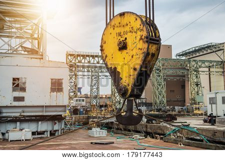 Huge industrial crane hook in the port for container cargo lifting.
