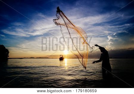 Fishing wtih net at the sea on a low tide at sunset silhoette of fishermen. Krabi province Thailand.