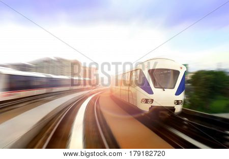 Modern light rail train on the move with bright sunlight glare