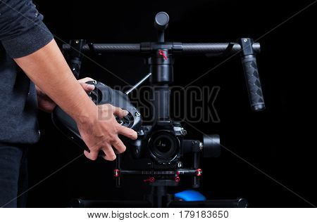 Potographer using hand held camera stablizer equipment for photography with remote control
