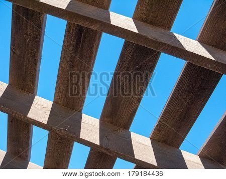 Blue sky as seen through weathered top of wooden pergola