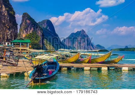 Longtail boats docked in Krabi Thailand with beautiful mountains in the background