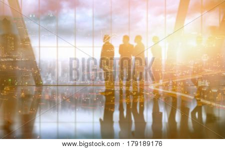 High angle view of illuminated cityscape against composite image of business colleagues talking