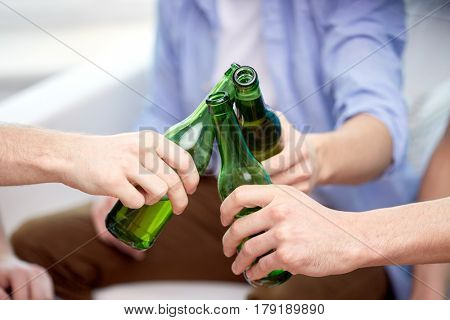 people, celebration and alcohol concept - close up of friends clinking beer bottles at home