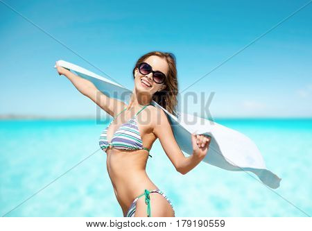 people, summer holidays and vacation concept - beautiful woman in bikini and sunglasses with towel on beach over blue sky and sea background
