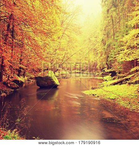 Autumn Mountain River With Blurred Waves, Stones And Boulders On Bank With Colorful Leaves