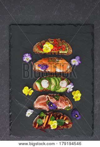 Rye bread sandwiches with avocado and cheese cream, prosciutto and salmon fish, edible flower garnish. Top view, blank space