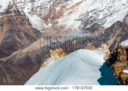 View of snowcapped Mountain Ridge with focus on it and desert rocky Valley below