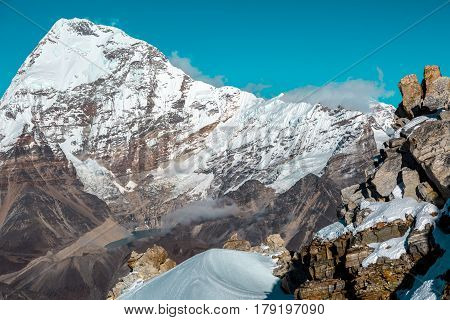 High Altitude Mountain Landscape Stone Rock and snowcapped Slope on foreground and majestic massive Peak on Background