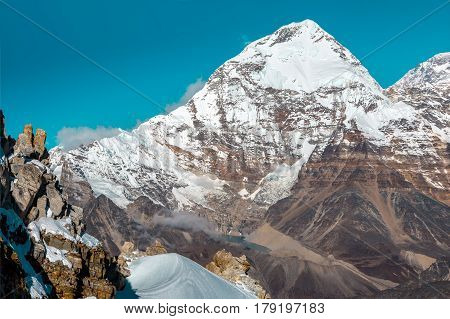 Layered Mountains Landscape with View of Rock and Snow Ridge on Foreground and majestic high snowcapped Peak on Background typical for Asia Himalayas or Tibet Ands and America.