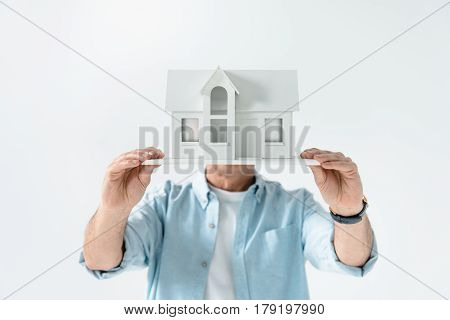Obscure View Of Man Showing House Model On White