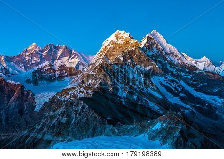 Himalaya Mountains Scenery in sunset Light spiked snowcapped Peaks with severe rocky and ice Walls
