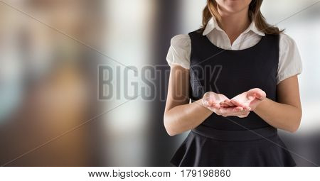 Digital composite of Business woman mid section in pinafore holding out hands in blurry room