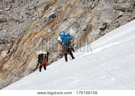 Nepalese professional Mountain Porters climbing Glacier carrying heavy Luggage of high Altitude Expedition poster